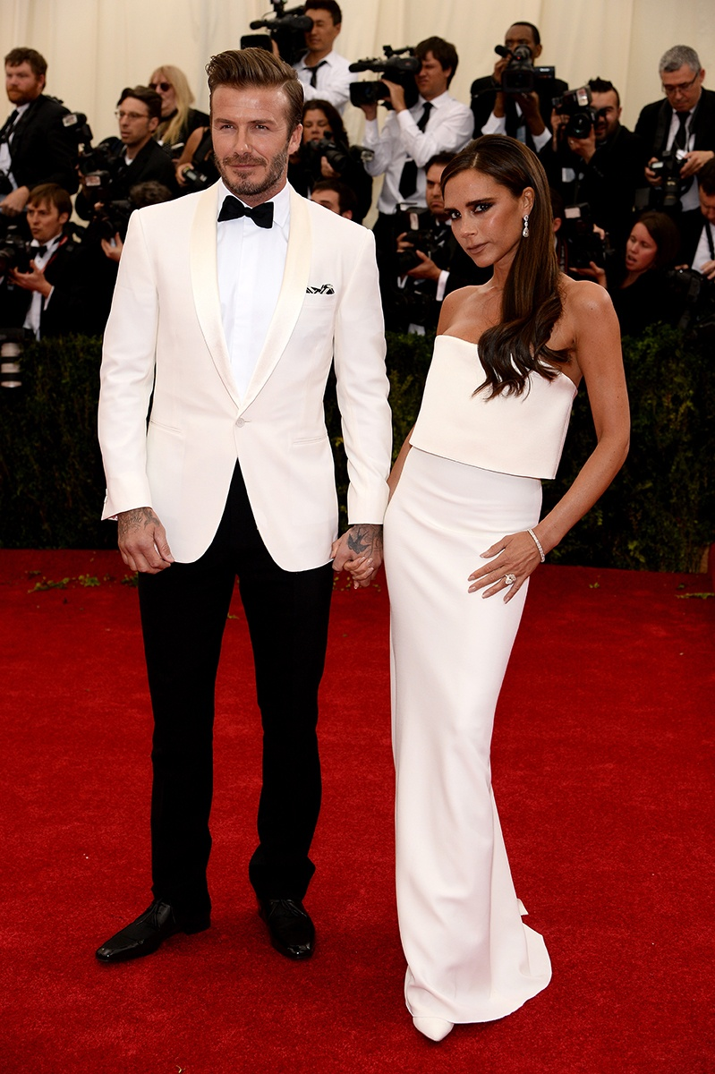 David Beckham in a Ralph Lauren Black Label suit and Christian Louboutin shoes and Victoria Beckham in Victoria Beckham